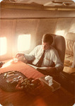 Max Baucus reading on a plane by Creator unknown