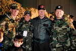 Bill Clinton and Max Baucus with service members by Creator unknown